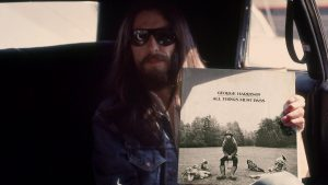 George Harrison holding his album