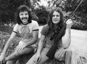 Tony Iommi and ozzy handling a gun